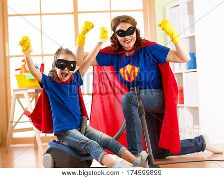 Strong superhero housewife and her kid daughter ready to room cleaning. Housework and household concept.