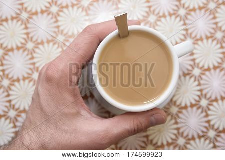 Hand holding cup of instant coffee with milk