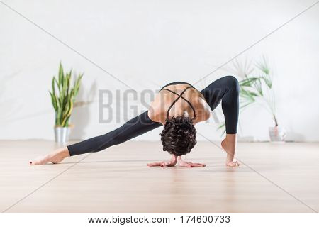 Fit modern dancer standing gracefully on tiptoe in wide side lunge facedown pose indoors