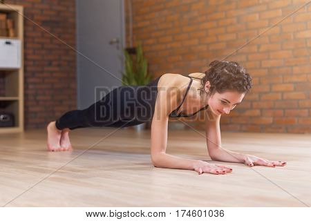 Fit woman doing yoga or pilates exercise standing in plank pose called phalankasana working out on floor in living room at home.