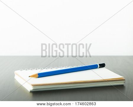 Bue pencil on a notebook with copy space