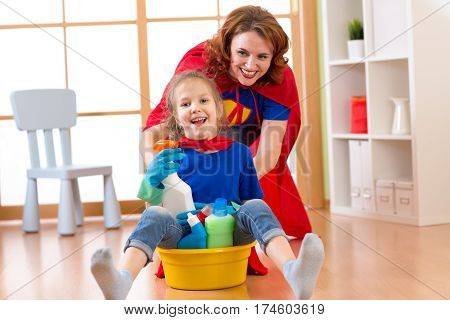 Beautiful mother and child little daughter dressed like superheroes cleaning and playing