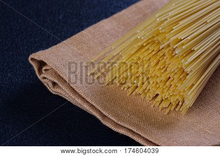 uncooked pasta on a cloth on a black background