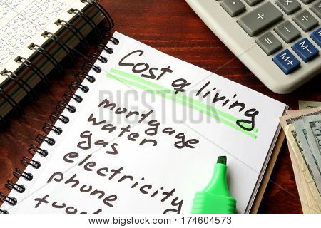 Cost of living written in a notebook and calculations of home finances.