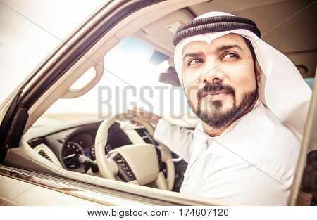 Arabic man in his luxury car watching outside