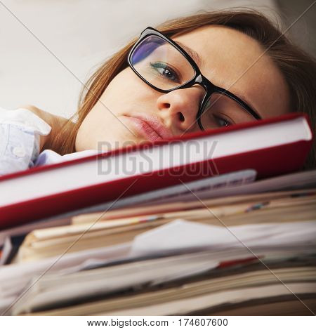 I want to sleep. Young business woman tired from office work with documents. Low wages overtime working hours lack of career prospects concept. (Body language gestures psychology concept)