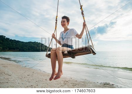 Happy girl on a swing tropical island phu quoc
