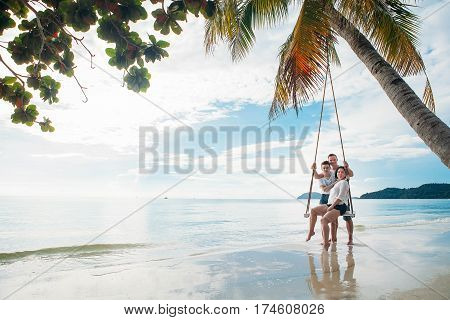 Family sit on Swing tropical beach phu quoc