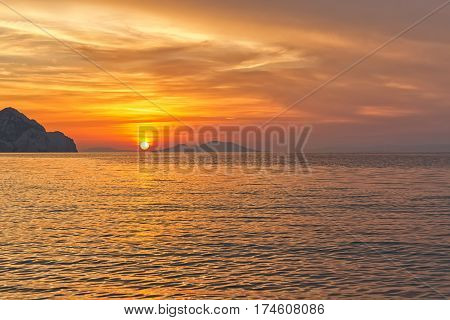 Sunset on the beach with beautiful dramatic yellow and orange sky. Silhouette of an island far ahead in sight.