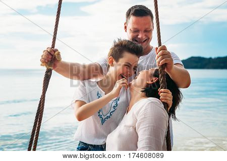 Family laughing siting on Swing tropical beach phu quoc