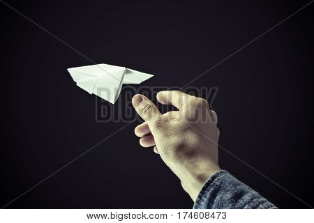 Image of a hand is throwing white paper plane on black background.