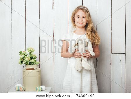 Cute little girl with a bunny rabbit toy on white wood background.