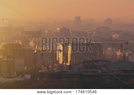 Close-up shooting from top of morning metropolitan city: huge stadium under construction with cranes and beams residential buildings and districts multiple facades hazy horizon Moscow Russia