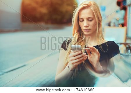 Pensive beautiful blonde caucasian girl sitting in street bar and texting message to her friend thoughtful freelancer woman browsing site on her smart phone in cafe with copy space for your message