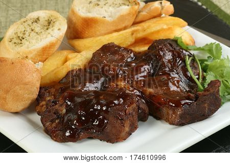 boneless beef ribs in barbecue sauce with fries and garlic bread