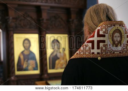 Orthodox bishop praying in front of altar icons in the church