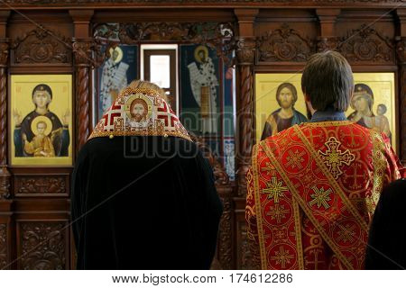 Orthodox bishop and archdeacon praying in front of altar