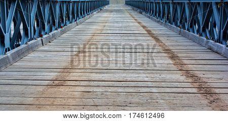 Bridge of El Chalten. One-step bridge. Wooden bridge with earth marks on it. Blue beams.