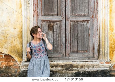 Beautiful girl in sundress talking on a smartphone on the background of the old city wall.