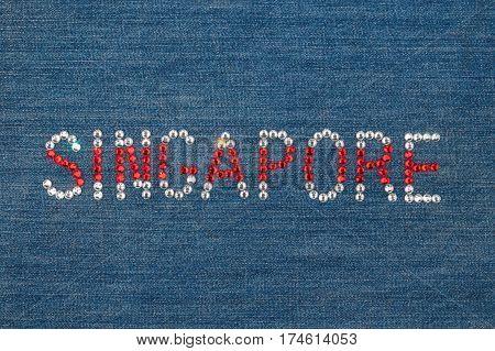 Inscription Singapore inlaid rhinestones on denim. View from above