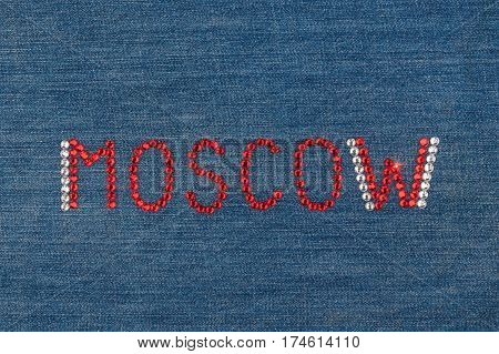 Inscription Moscow inlaid rhinestones on denim. View from above