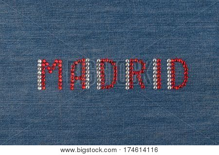 Inscription Madrid inlaid rhinestones on denim. View from above