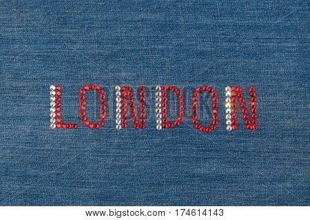Inscription London inlaid rhinestones on denim. View from above