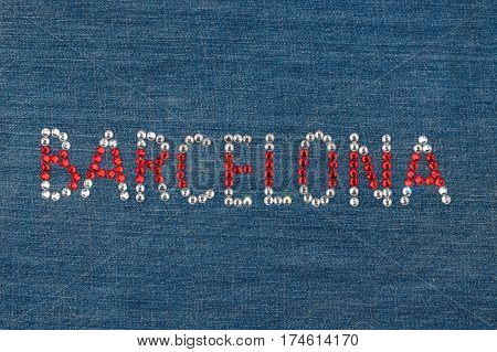 Inscription Barcelona inlaid rhinestones on denim. View from above
