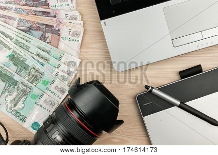 Work table designer photographer and earned money rubles. View from above