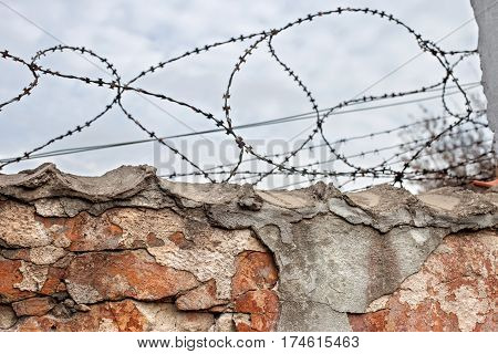 ancient brick wall with barbed wire close up