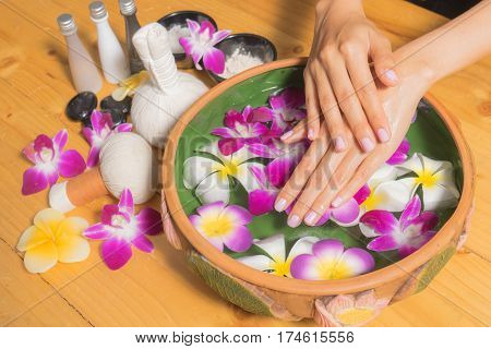 Woman Hands With A Bowl Of Aroma Spa Water Oil On Wooden Table