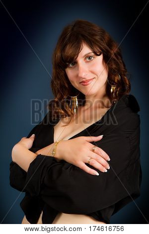 young beautiful girl in a black man's shirt on a dark background