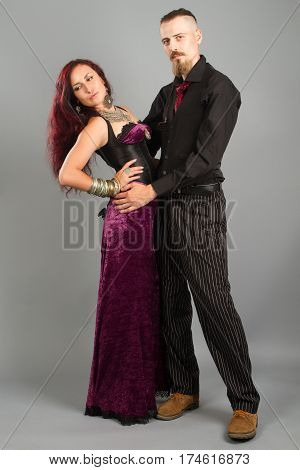 Portrait of young couple in love posing at studio dressed in classic clothe