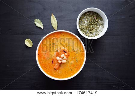 Homemade soup with white beans and vegetables in white bowl on a black wooden background.