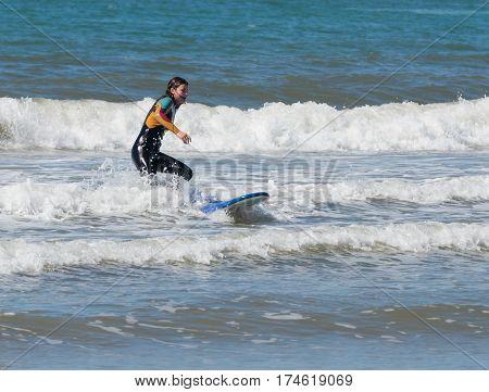Girl In Color Waterproof Suit Exercising In Surfing On Board