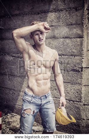 Handsome muscular construction worker standing shirtless in front of a concrete wall, looking away to a side, drying sweat from his forehead