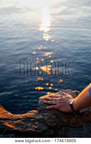 Close up shot of men's left hand on a rock, wearing a simple wedding band and a watch. Sea, sunset and light trails on the background.