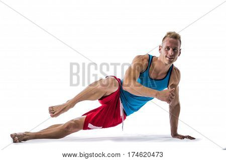 Blond athletic young man exercizing on the floor, isolated on white background in studio shot