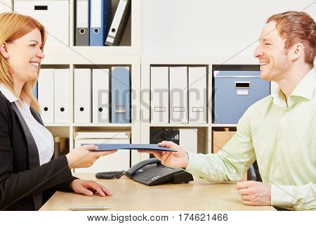 Woman giving her application portfolio to the interviewer in a job interview
