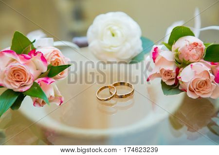 Wedding boutonniere and wedding rings on glass.