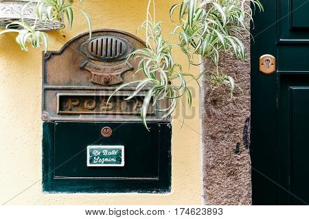 Green metal letterbox beside a green door over a yellow wall in Italy