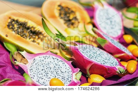 The cross section of dragon fruit or pitahaya with on the background the cross section of a papaya