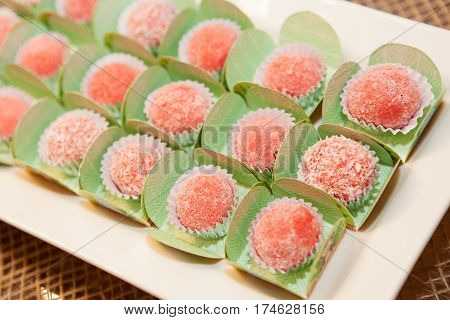 Strawberry candies in green wraps on table