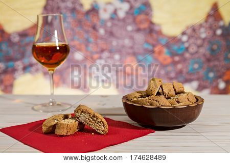 Italian cantucci biscuits over a red napkin and a glass of vin santo wine on background