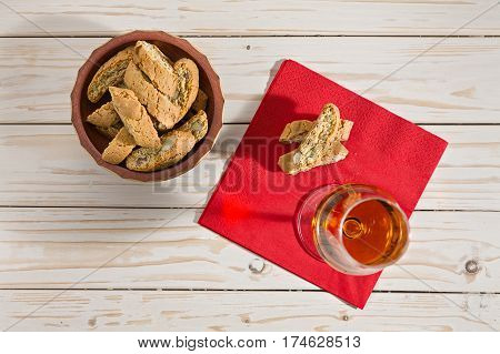 Italian cantucci biscuits and vin santo wine over a red napkin seen from above