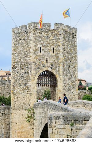 BESALU, SPAIN - AUGUST 17, 2016: People on the bridge of Besalu. The town's most significant feature, its 12th-century Romanesque bridge over the Fluvia river, which features a gateway at its midpoint.