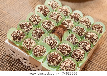 Chocolate candies in green wraps on table