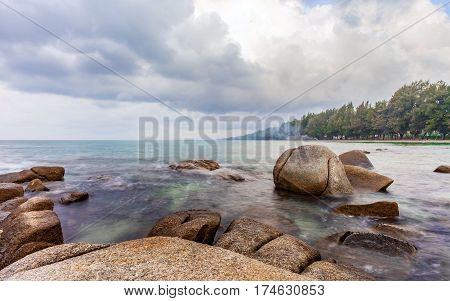 sea in the morning sunrise with cloudy sky and rocks rayong province thailand