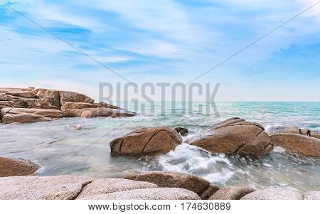 sea in the morning sunrise with bright blue sky and rocks rayong province thailand