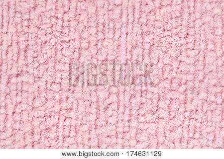 Light pink fluffy background of soft fleecy cloth. Texture of textile closeup.